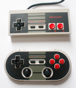 Side-by-side comparison of the 8Bitdo with the original NES controller.